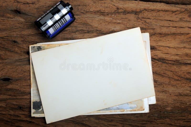 与照相机影片的老纸照片框架在木背景 库存图片