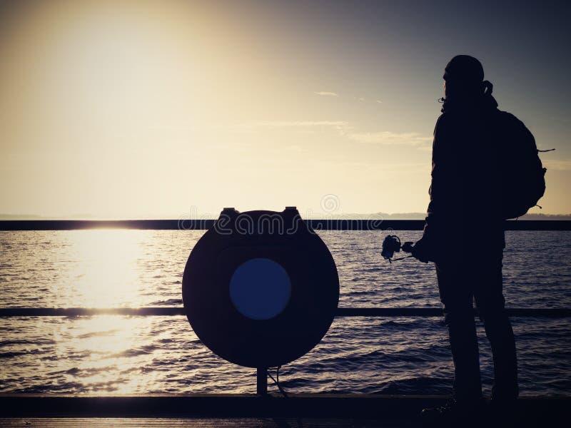 与照相机的弯成拱状的艺术家照片在三脚架 扶手栏杆的游人 免版税库存照片