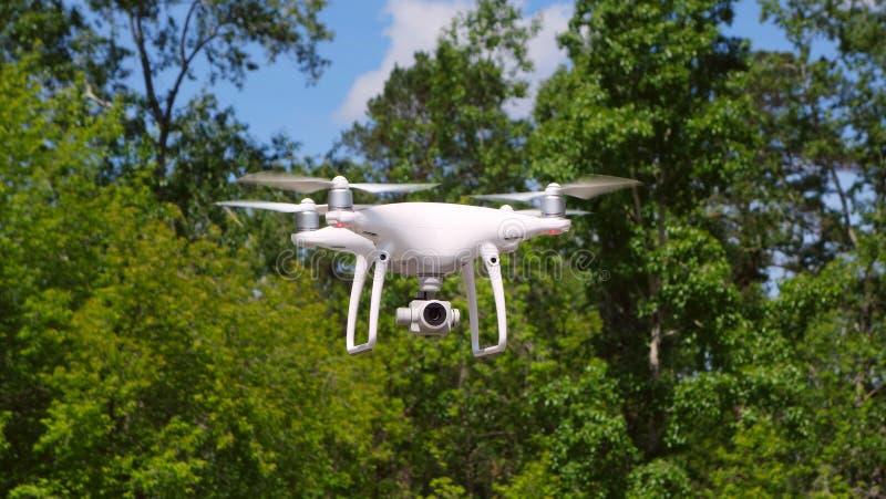 与照相机的Quadrocopter寄生虫 现代RC寄生虫 反对绿色被弄脏的背景的直升机飞行 库存照片