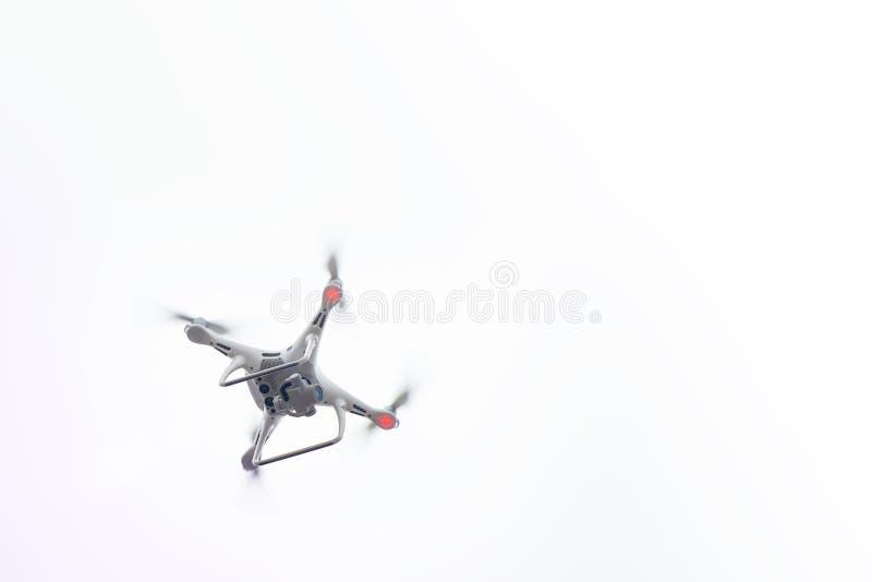 与照相机飞行的白色寄生虫在蓝天 UAV概念 免版税库存图片