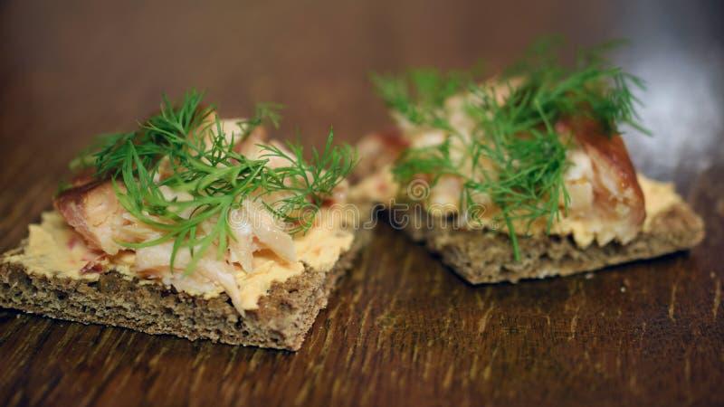 与熏制的红点鲑、奶油奶酪和莳萝的黑麦面包点心 免版税库存照片