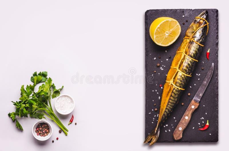 与熏制的鲭鱼鱼和香料的灰色食物背景 免版税库存图片