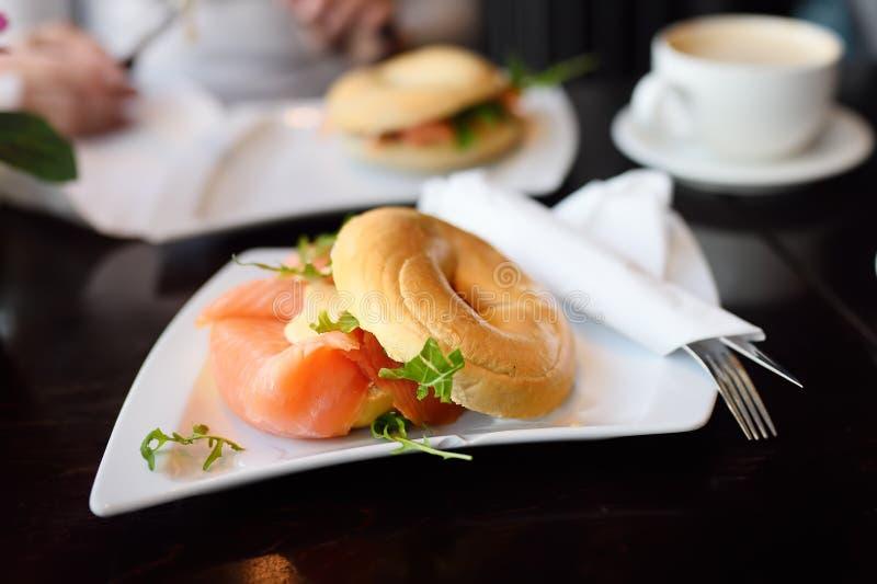 与熏制鲑鱼、奶油奶酪和芝麻菜的新近地被烘烤的百吉卷 库存图片