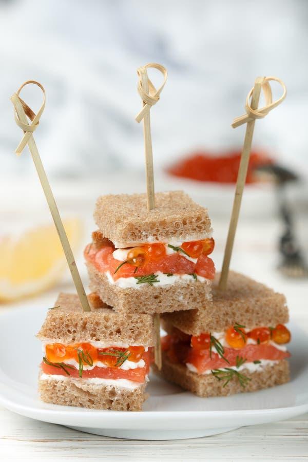 与熏制鲑鱼、软干酪、莳萝和鱼子酱的黑麦面包点心 库存图片