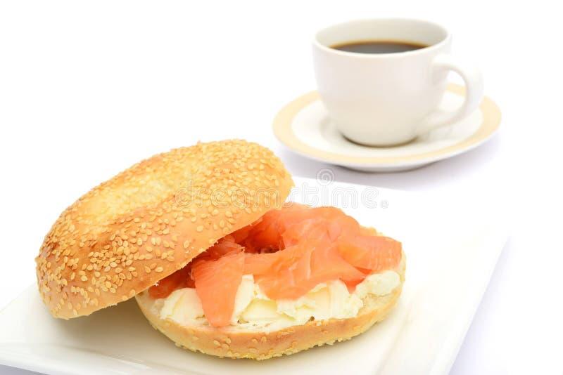 与熏制鲑鱼和咖啡的百吉卷 免版税库存照片