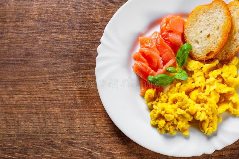 与熏制鲑鱼和多士的炒蛋在木桌上的白色板材 免版税图库摄影