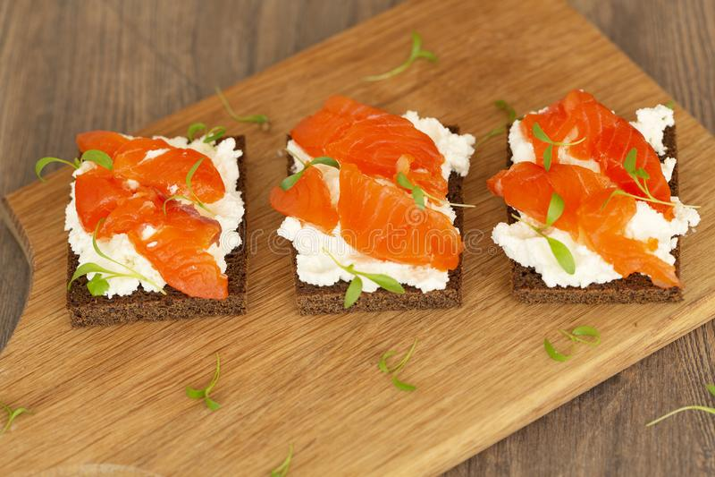 与熏制鲑鱼和奶油奶酪的点心在木板 r 免版税库存图片