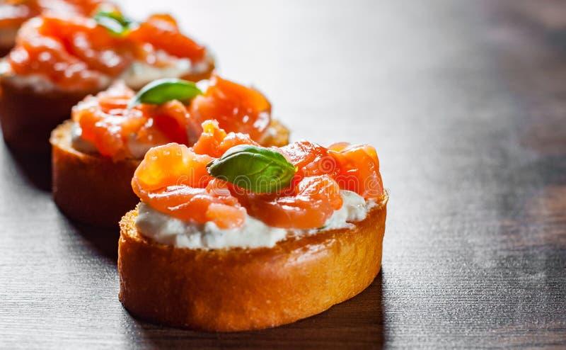 与熏制鲑鱼和奶油奶酪的点心在木桌上 免版税库存照片