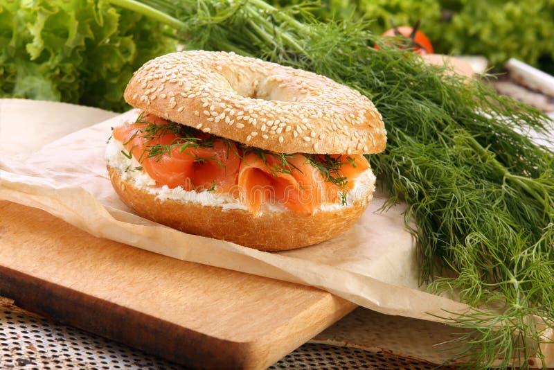 与熏制鲑鱼和莳萝的三明治在一块砧板 图库摄影