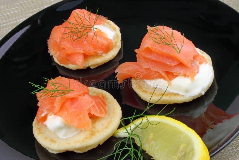 与熏制鲑鱼的俄式薄煎饼 免版税库存照片
