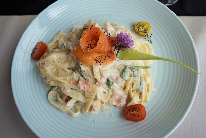 与熏制鲑鱼的Tagliatelle在乳脂状的乳酪调味料 免版税库存图片