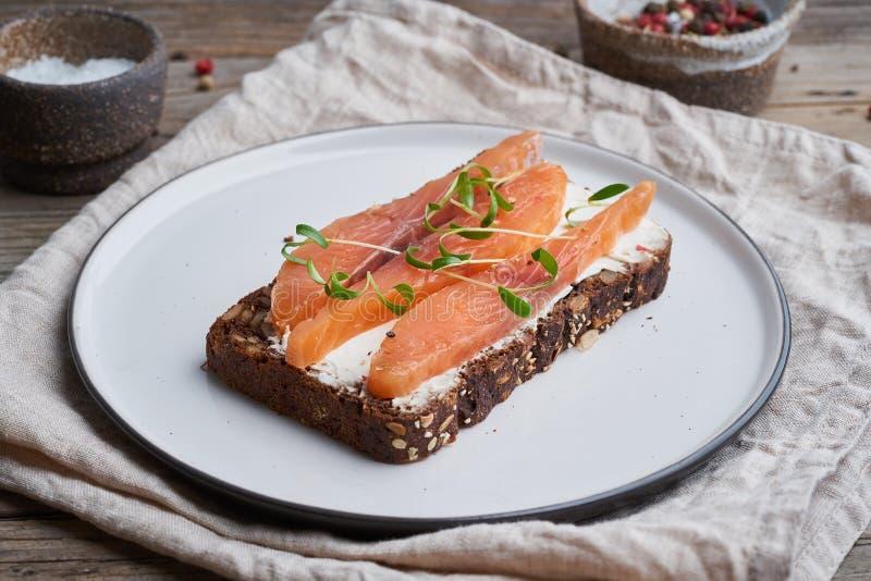 与熏制鲑鱼,在老木桌上的奶油奶酪的黑麦面包 Smorrebrod,开放丹麦三明治,侧视图 库存图片
