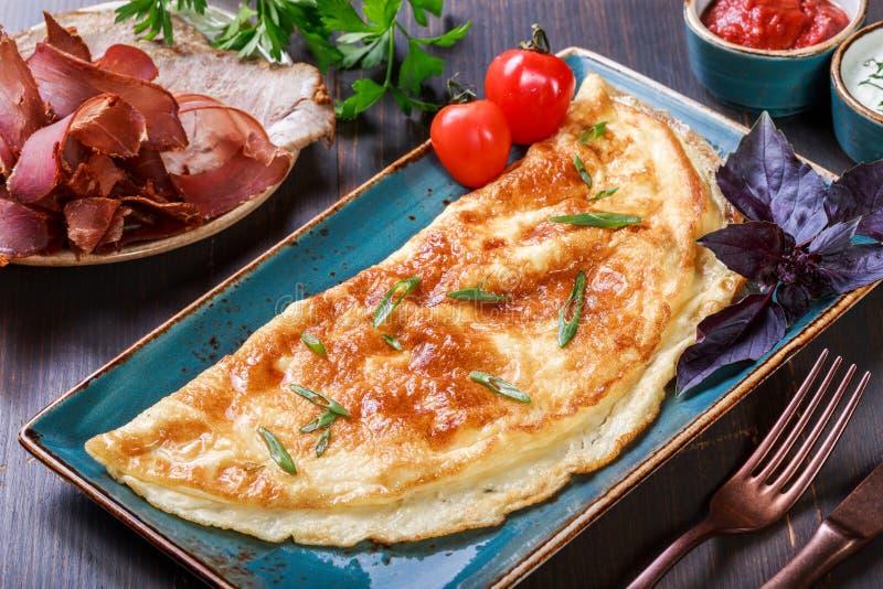 与熏火腿、切片火腿,蘑菇、绿色、乳酪和西红柿酱的煎蛋卷在黑暗的木背景 库存照片