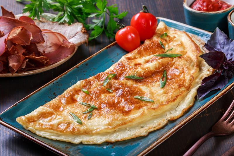 与熏火腿、切片火腿,蘑菇、绿色、乳酪和西红柿酱的煎蛋卷在黑暗的木背景 库存图片