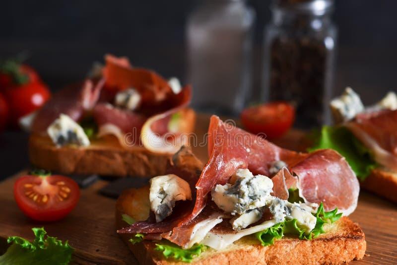 厨桌上放着烤火腿、沙拉烤饼和奶酪的烤面包 零食 库存照片
