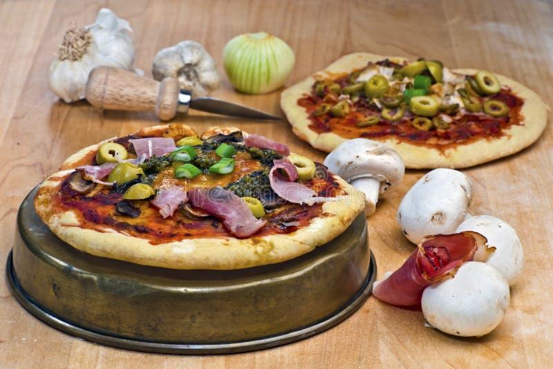 与熏火腿、蘑菇、橄榄、pesto和乳酪t的微型薄饼 免版税图库摄影