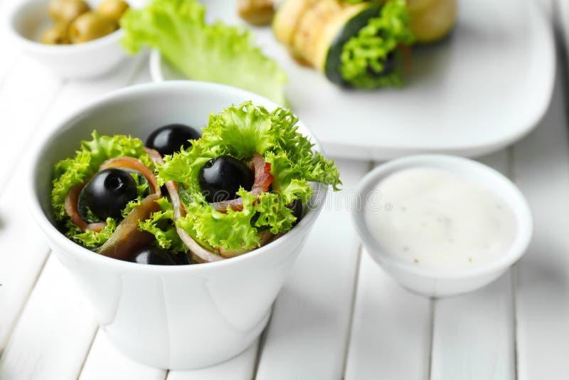 与熏火腿和橄榄的鲜美夏南瓜卷在白色桌上的碗 免版税库存图片