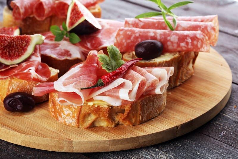 与熏火腿的三明治或蒜味咸腊肠或者crudo 开胃小菜食家b 免版税库存照片