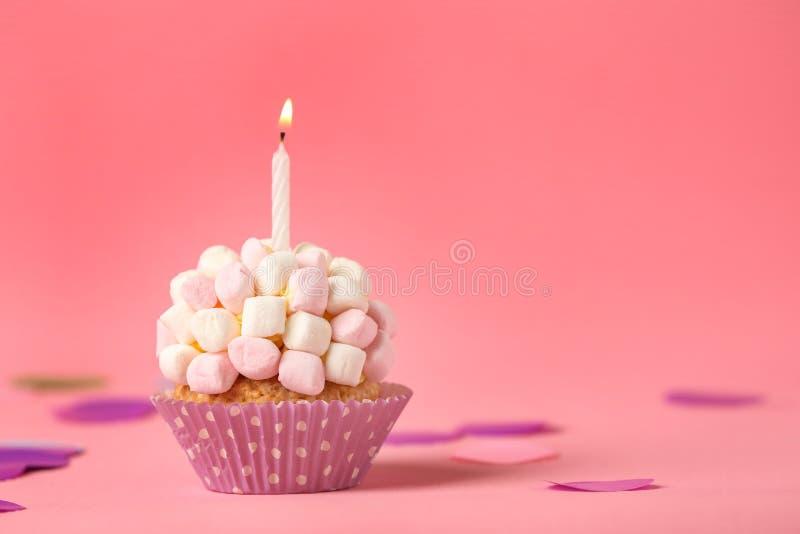 与燃烧的蜡烛和蛋白软糖的可口生日杯形蛋糕在颜色背景 免版税库存图片