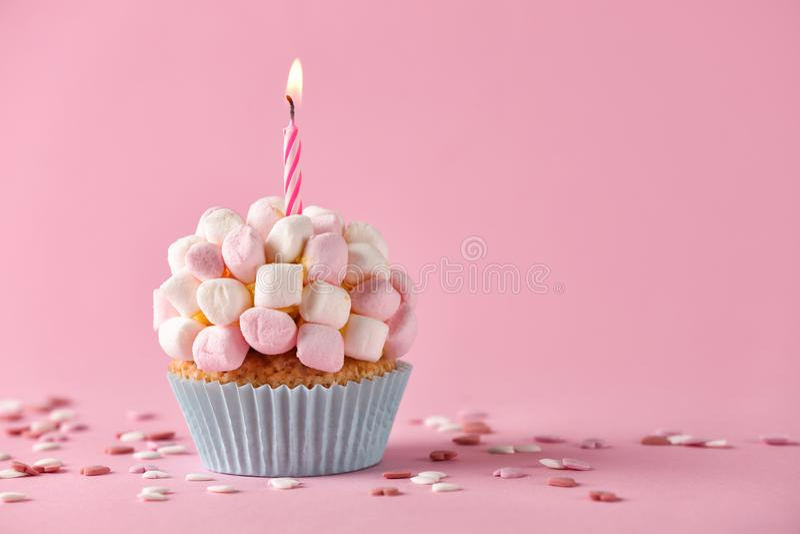 与燃烧的蜡烛和蛋白软糖的可口生日杯形蛋糕在颜色背景 库存图片