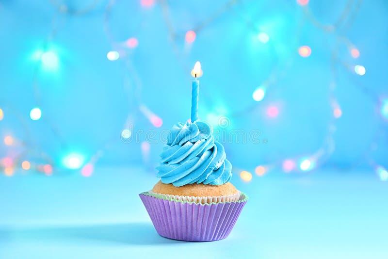 与燃烧的蜡烛的可口生日杯形蛋糕反对被弄脏的光 库存照片
