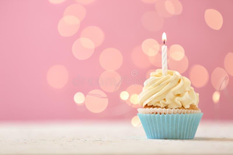 与燃烧的蜡烛的可口生日杯形蛋糕反对被弄脏的光 免版税库存图片