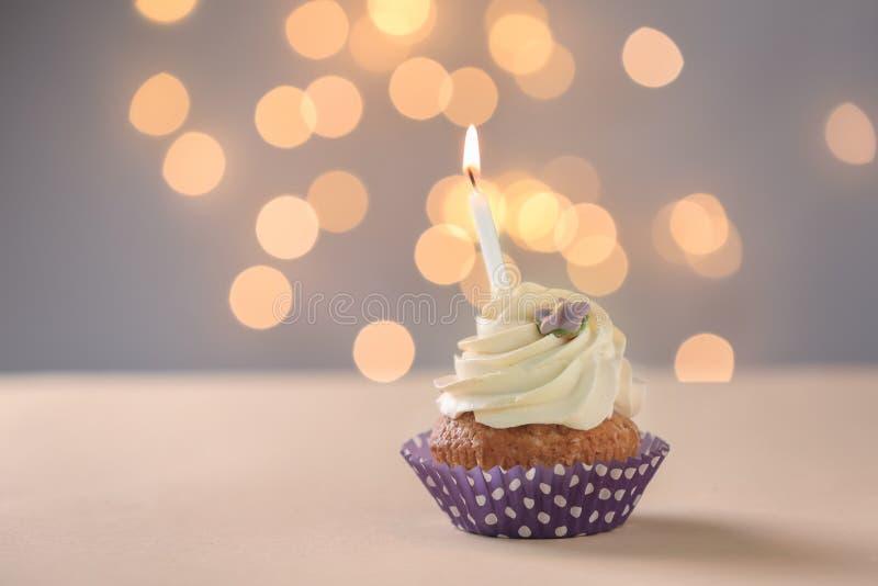 与燃烧的蜡烛的可口生日杯形蛋糕在反对被弄脏的光的桌上 免版税库存图片