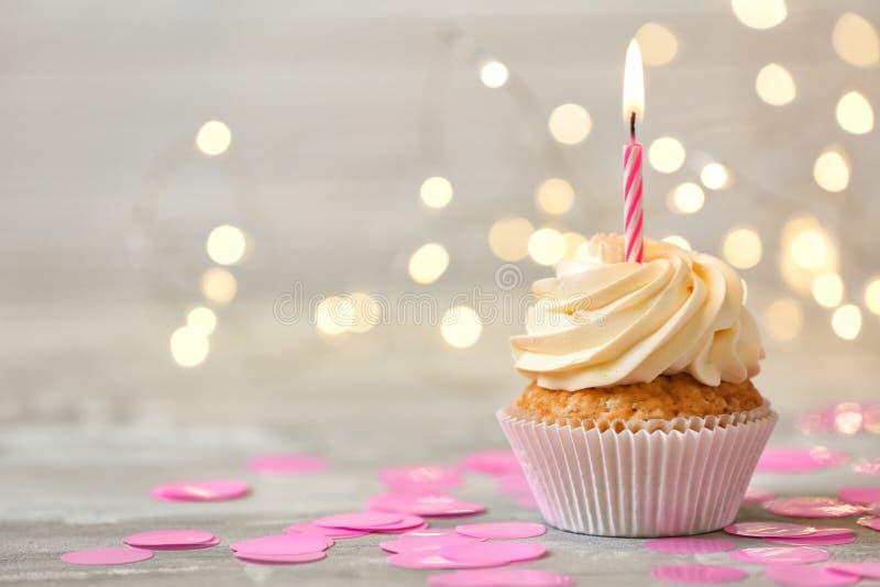 与燃烧的蜡烛的可口生日杯形蛋糕在反对被弄脏的光的灰色桌上 库存图片