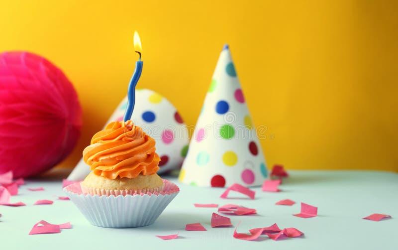 与燃烧的蜡烛的可口生日杯形蛋糕在反对颜色背景的桌上 库存图片