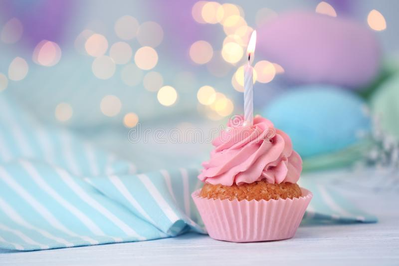 与燃烧的蜡烛的可口生日杯形蛋糕在桌上 免版税库存图片