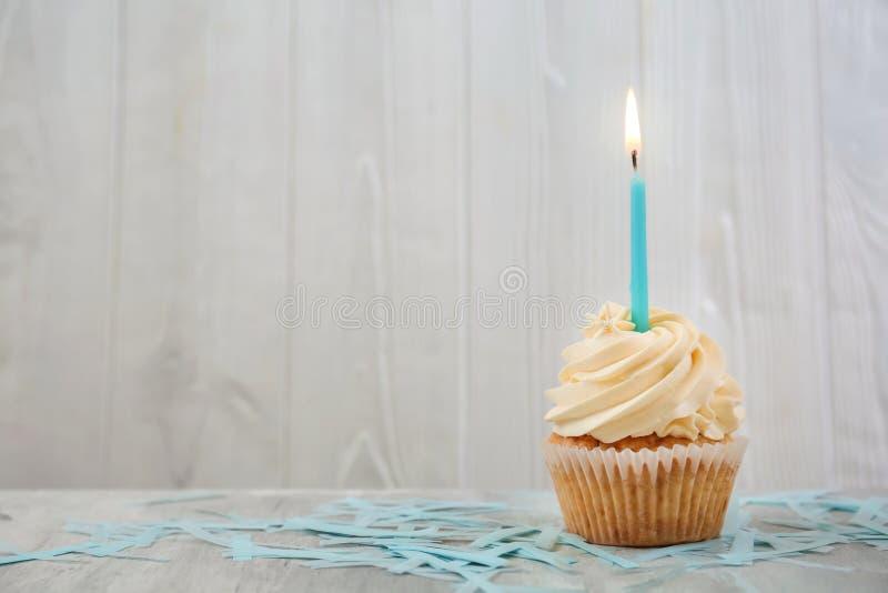 与燃烧的蜡烛的可口生日杯形蛋糕在桌上 免版税图库摄影