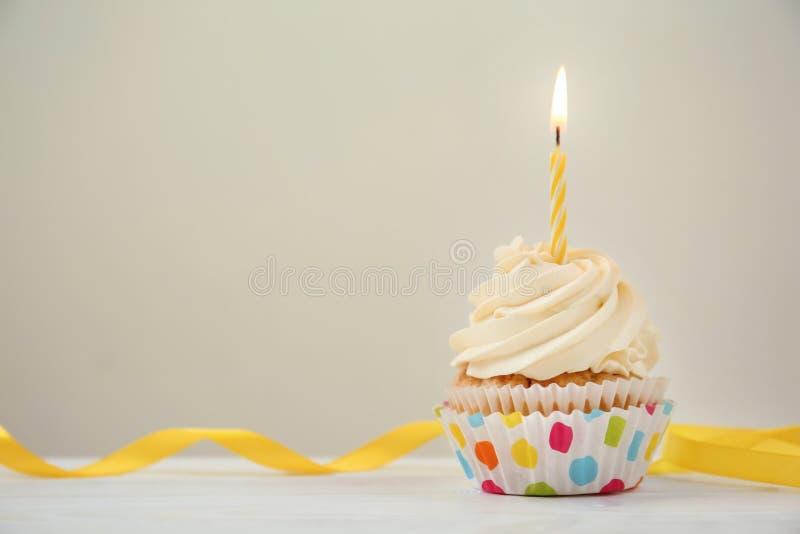 与燃烧的蜡烛的可口生日杯形蛋糕在白色木桌上 库存照片