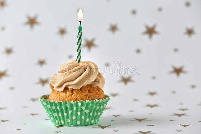 与燃烧的蜡烛的可口生日杯形蛋糕在轻的背景 免版税库存照片
