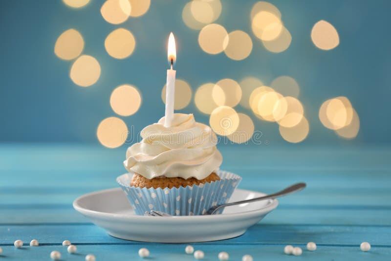 与燃烧的蜡烛的可口生日杯形蛋糕在颜色木桌上 免版税库存照片