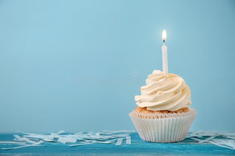 与燃烧的蜡烛的可口生日杯形蛋糕在颜色木桌上 库存照片