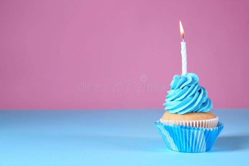 与燃烧的蜡烛的可口生日杯形蛋糕在颜色背景 图库摄影