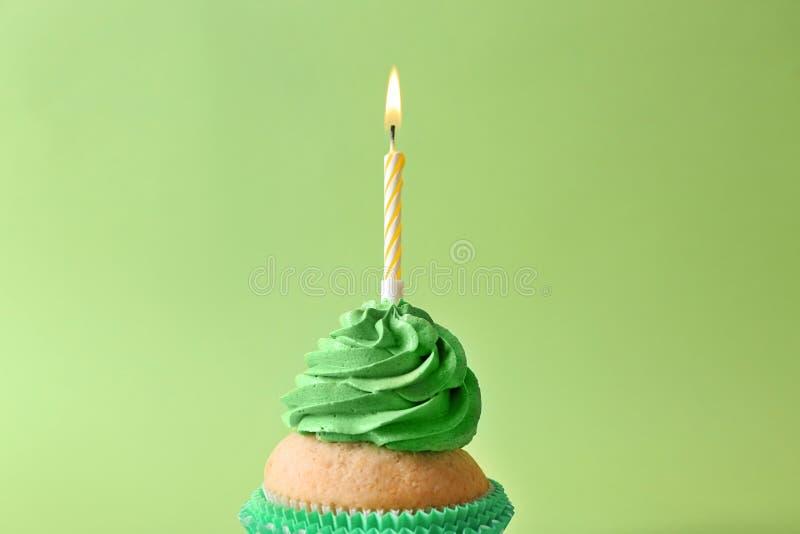 与燃烧的蜡烛的可口生日杯形蛋糕在颜色背景 库存照片