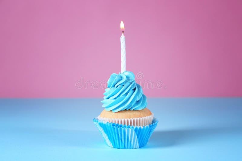 与燃烧的蜡烛的可口生日杯形蛋糕在颜色背景 库存图片