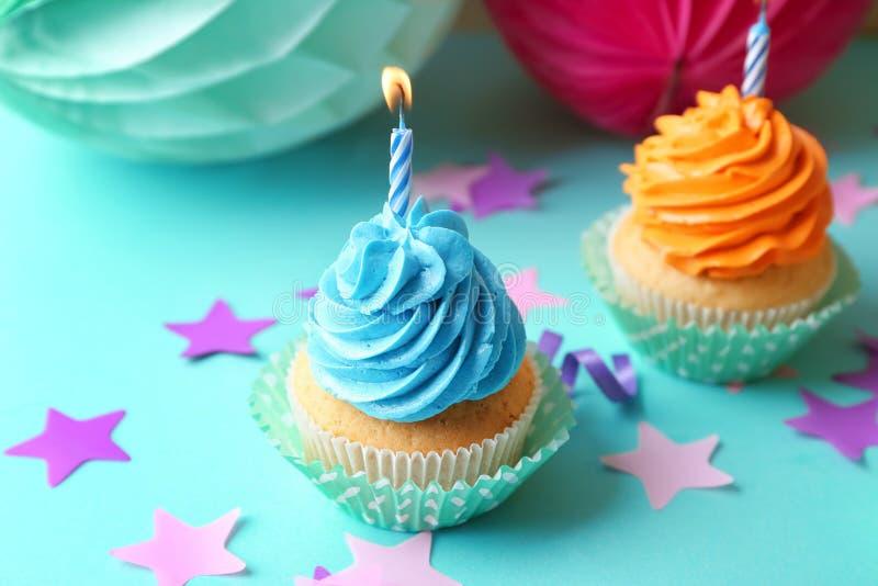 与燃烧的蜡烛的可口生日杯形蛋糕在颜色背景 免版税库存照片
