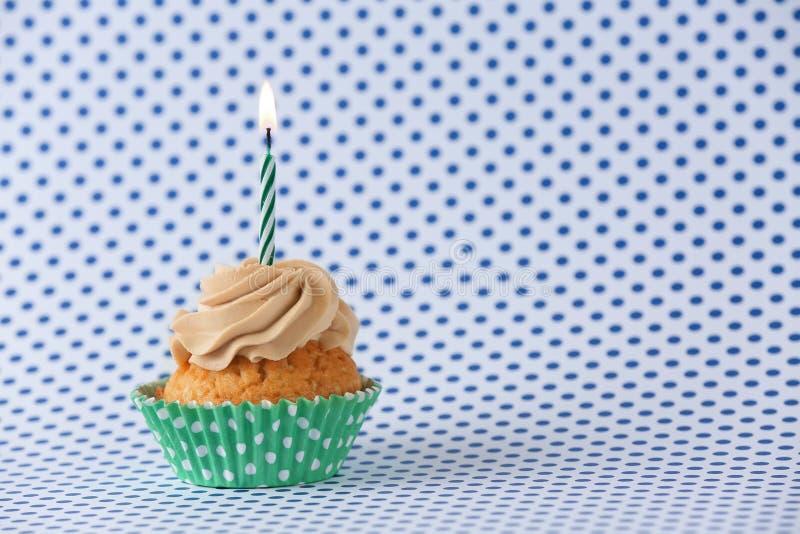 与燃烧的蜡烛的可口生日杯形蛋糕在颜色背景 免版税库存图片