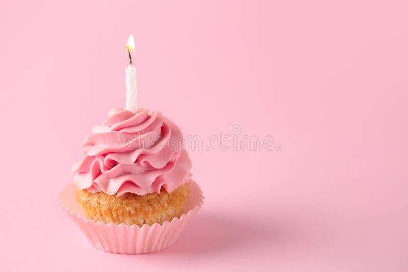 与燃烧的蜡烛的可口生日杯形蛋糕在颜色背景 免版税图库摄影