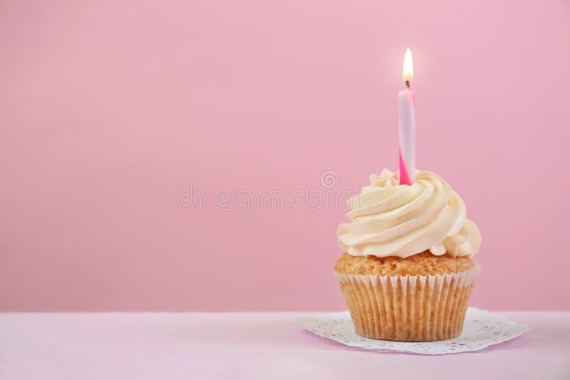 与燃烧的蜡烛的可口生日杯形蛋糕在颜色表上 免版税库存照片