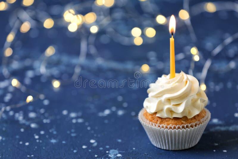 与燃烧的蜡烛的可口生日杯形蛋糕在颜色表上 免版税图库摄影