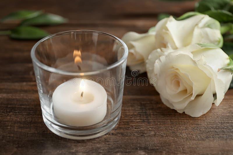 与燃烧的蜡蜡烛的玻璃持有人在木桌上的玫瑰附近 免版税图库摄影