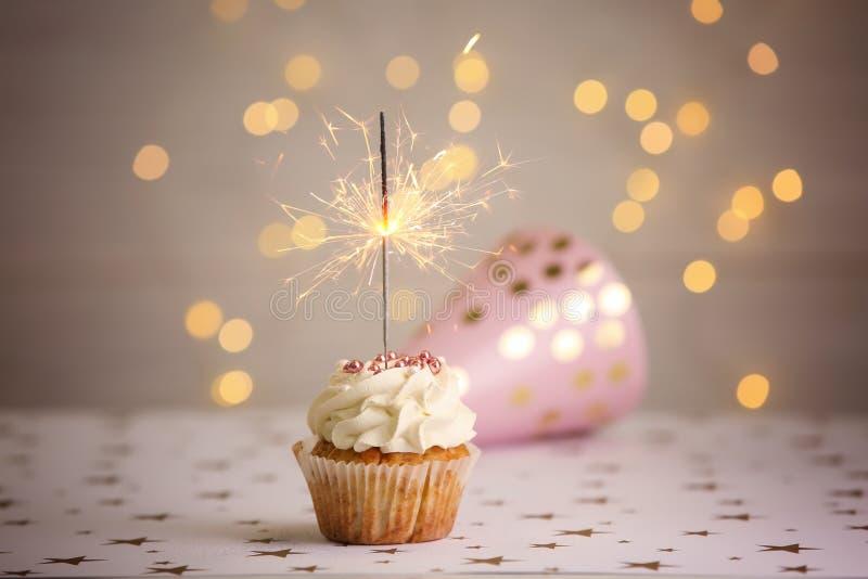 与燃烧的闪烁发光物的可口生日杯形蛋糕在桌上 免版税库存照片