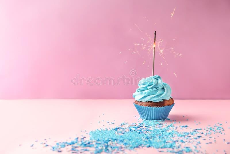 与燃烧的闪烁发光物的可口生日杯形蛋糕在颜色背景 库存图片