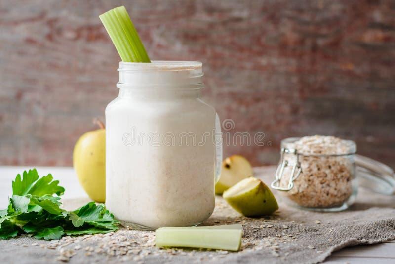 与燕麦剥落、苹果和芹菜的圆滑的人 库存图片