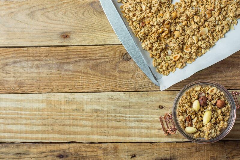 与燕麦榛子杏仁核桃混合物的自创格兰诺拉麦片Muesli在烘烤在玻璃瓶子排行的与纸和Trey 木表 免版税库存照片