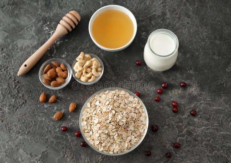 与燕麦粥剥落、坚果、牛奶和蜂蜜的构成在黑暗的织地不很细背景 库存图片