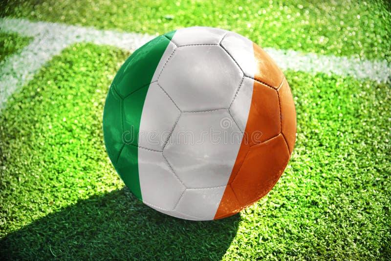 与爱尔兰的国旗的橄榄球球在绿色领域说谎 库存图片
